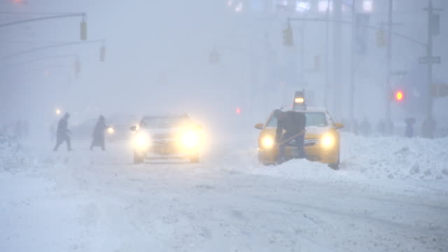 camera captures traffic of 6th avenue during the serious winter snowstorm jonas.road and cars were covered by snow and visibility is bad for snowing.a taxi stuck in the deep snow. - feststecken stock-videos und b-roll-filmmaterial