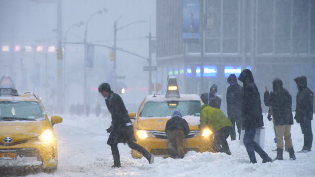 vídeos de stock e filmes b-roll de camera captures traffic of 6th avenue during the serious winter snowstorm jonas.road and cars were covered by snow and visibility is bad for snowing.people help to escape the stacked taxi from deep snow. - pá para neve