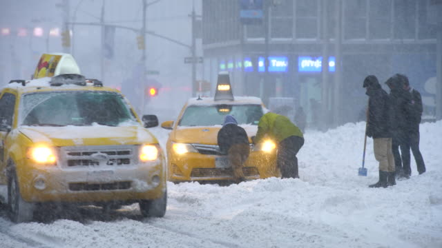 camera captures traffic of 6th avenue during the serious winter snowstorm jonas.road and cars were covered by snow and visibility is bad for snowing.people help to escape the stacked taxi from deep snow. - bloccato video stock e b–roll