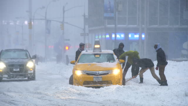 Camera captures traffic of 6th Avenue during the serious winter snowstorm Jonas.Road and cars were covered by snow and visibility is bad for snowing.People help to escape the stacked taxi from deep snow.