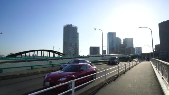 Camera captures traffic of Harumibashi Bridge over the Harumi Canal, which is connects Tsukishima, Chuo ward and Toyosu, Koto ward Tokyo. Chuo ward high-rise buildings can be seen beyond the Harumi Canal at Chuo, Tokyo, Japan.