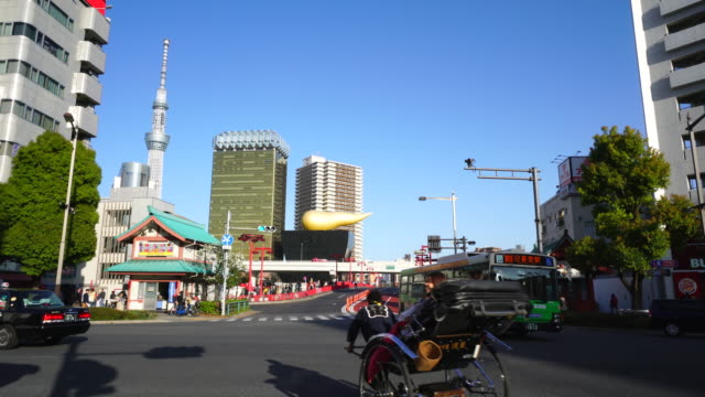 camera captures traffic of kaminarimon-dori and edo-dori intersection in asakusa, taito-ku tokyo. tokyo sky tree and asahi beer tower can be seen behind tokyo expressway. rickshaw crosses the intersection. - rickshaw stock videos and b-roll footage