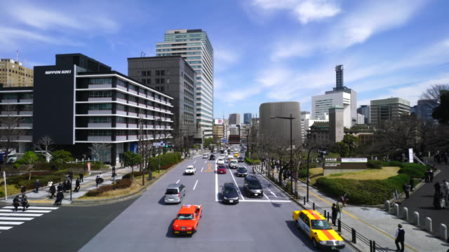 camera captures traffic of the yasukuni doori toward to the kanda jimbocho area. clouds move at clear blue sky. kitanomaru park can be seen right side. - 集合住宅点の映像素材/bロール