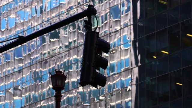 vídeos de stock e filmes b-roll de camera captures traffic signal and streetlight in front of building's reflection at midtown manhattan new york. - sinal rodoviário