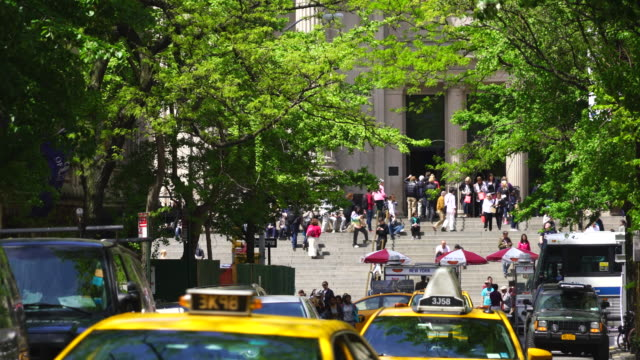 camera captures visitors at the entrance of the metropolitan museum through the fresh green trees of street manhattan new york. taxis run through the street, which are surrounded by fresh green trees. - metropolitan museum of art new york city stock videos & royalty-free footage
