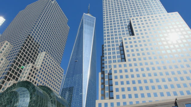 vídeos de stock, filmes e b-roll de pan camera captures world financial center buildings and one world trade center building. - distrito financeiro de manhattan