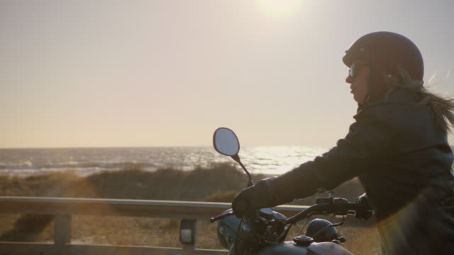SLO MO. Camera circles and pulls back as two women on motorcycles talk and laugh overlooking the ocean.