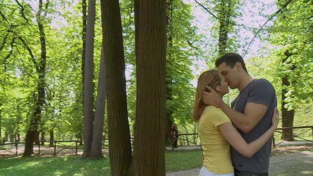 vidéos et rushes de ms camera circling embracing and kissing couple in park/ ljubljana, slovenia - embrasser sur la bouche