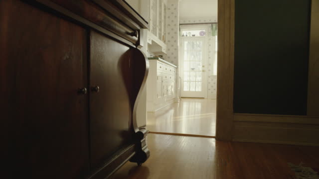 camera dollies from a vintage dining room, along a wooden floor and wooden bureau toward a the kitchen. - 整理ダンス点の映像素材/bロール