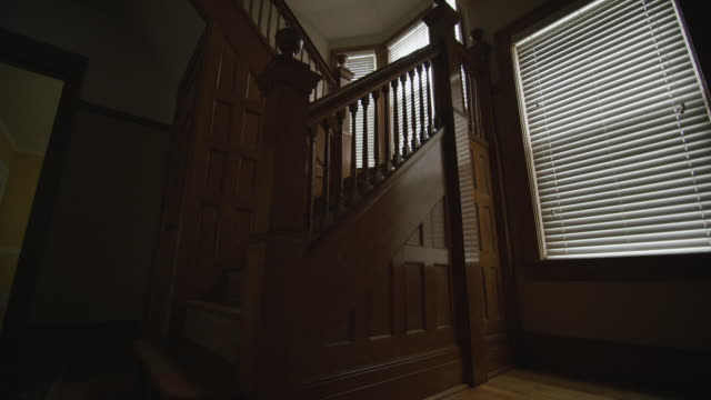 camera dollies left along vintage oak wainscoting, revealing a dark empty staircase and dining room in the background. - dining room stock videos & royalty-free footage