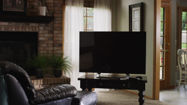 Camera dollies toward a large flat screen television in an empty living room with easy chair and fireplace.