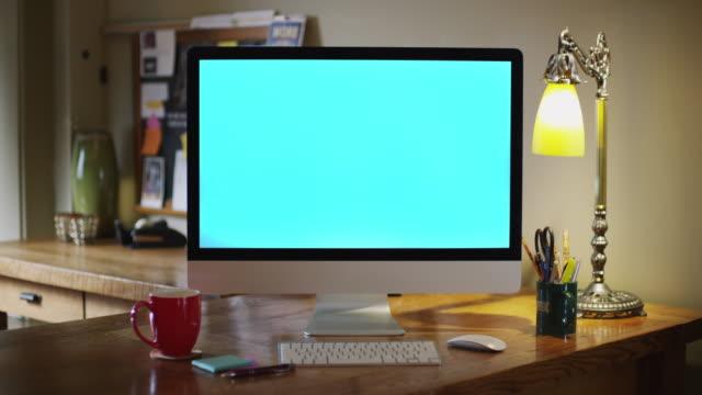 Camera dollies toward a workstation desktop computer screen in a business office.