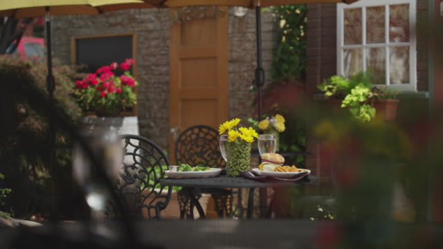 camera dollies toward an empty bistro table in an outdoor cafe. a large hamburger with french fries and a salad sit on the table. - elkhorn nebraska stock videos & royalty-free footage