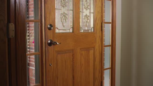 vidéos et rushes de camera dollies toward the front door of a home as a woman enters frame, opens the door, steps outside, closes the door, walks away. - porte entrée