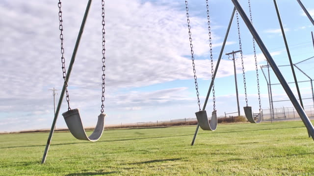 vídeos de stock e filmes b-roll de camera dolly past empty swings in a small town playground park. - equipamento de parque infantil