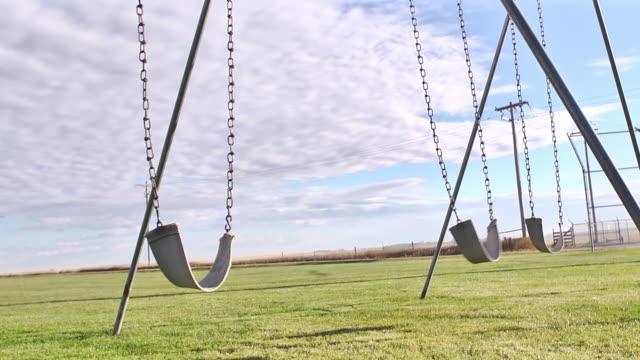 vídeos de stock e filmes b-roll de camera dolly past lonely empty swings in a small town playground park. - equipamento de parque infantil