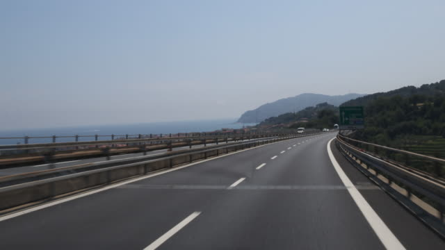 Camera drive with a van on a two lane highway in Italy at the coast at the Ligurian Sea the landscape and the sea can be seen on the left
