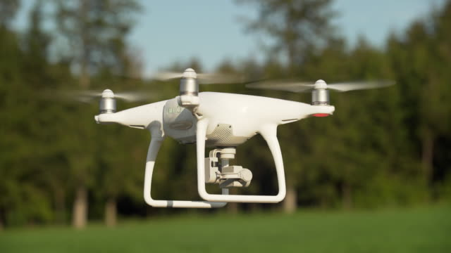 camera drone hovering in open country (4k/uhd) - quadcopter stock videos & royalty-free footage