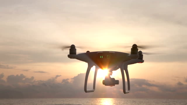 camera drone hovering in the sky at sunrise - flying stock videos & royalty-free footage