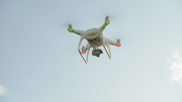camera drone hovering in the sky (4k/uhd) - hovering stock videos & royalty-free footage