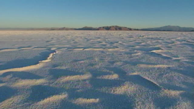 camera flies low over eerie, dramatic moonscape salt flats. - salt flat stock videos & royalty-free footage