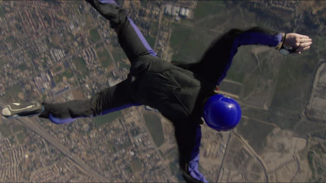 camera flies over and under skydiver in free fall - imbracatura di sicurezza video stock e b–roll