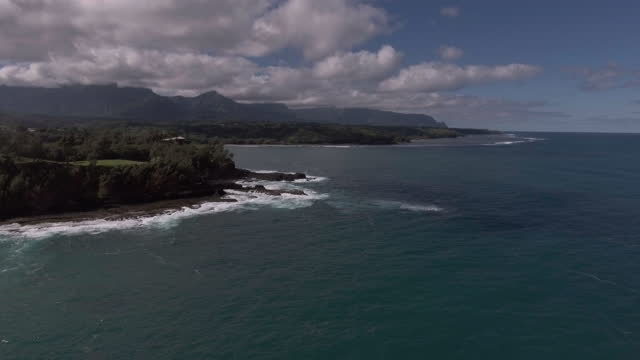 AERIAL. Camera flies over beautiful blue ocean by Kauai island shore with cloudy mountain range in distance.