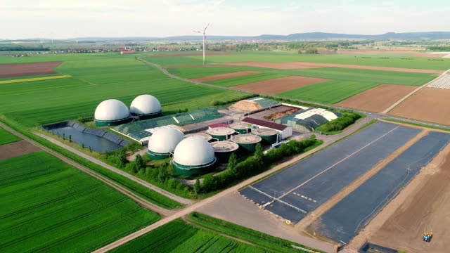 Camera flight over biogas plant from pig farm. Renewable energy from biomass. Modern agriculture European Union. aerial view, panoramic view from the air