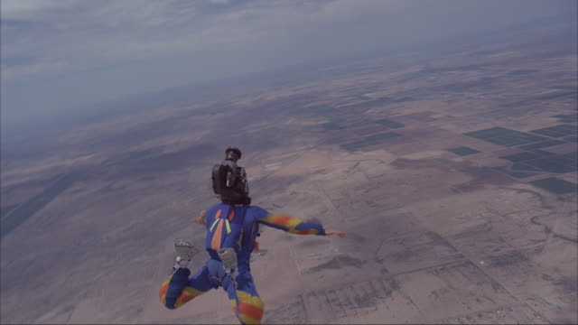 a camera flyer films a skydiver deploying his parachute, then deploy's his own. - parachute stock videos & royalty-free footage