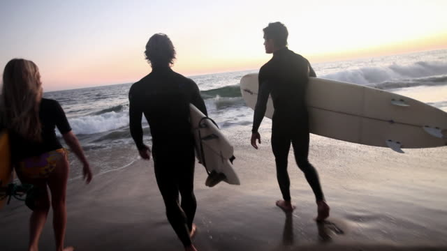 camera following three surfers as they go into the sea - malibu stock videos & royalty-free footage