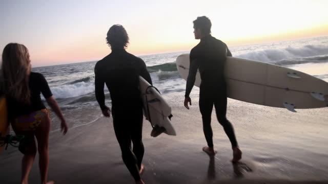 vidéos et rushes de camera following three surfers as they go into the sea - malibu