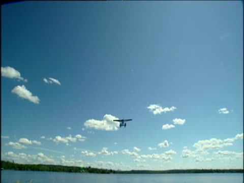 camera follows a water plane as it flies from lake overhead and into the opposite horizon. - bbc stock videos and b-roll footage