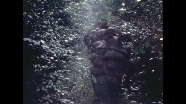 camera follows gis on patrol as they move along a narrow path through the dense jungle carrying rucksacks and weapons - ベトナム戦争点の映像素材/bロール