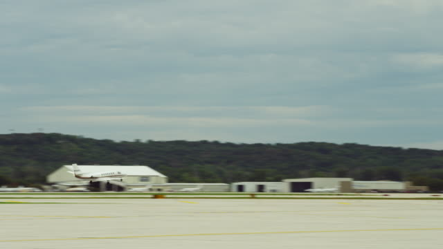 camera follows small private jet as it takes off down the runway and climbs into the sky. - private airplane stock videos & royalty-free footage