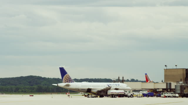 Camera follows small private jet just after take off from the runway; it flies away over an airline terminal.