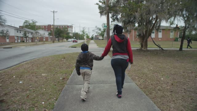 vídeos de stock, filmes e b-roll de slo mo. camera follows young african american mother and son as they walk down neighborhood sidewalk holding hands. - community