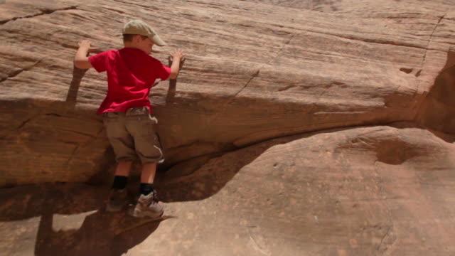 vídeos de stock e filmes b-roll de camera follows young hiker boy scaling the side of a rocky canyon wall - exploração