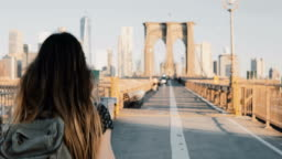 Camera follows young woman with backpack walking along Brooklyn Bridge, New York on a beautiful sunny summer day 4K