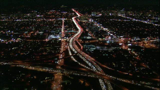 Camera glides northward above dense traffic on 405 freeway, river of light towards Westwood