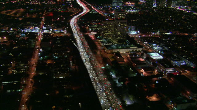 Camera glides northward above dense traffic on 405 freeway, river of light and past Westwood