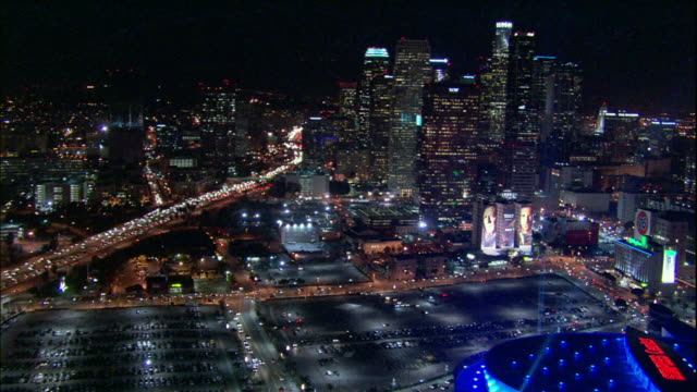 Camera glides over Staples Center and into downtown LA skyscrapers.