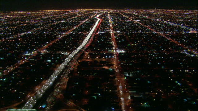 Camera glides southward above 110 freeway river of light and South Los Angeles sea of lights