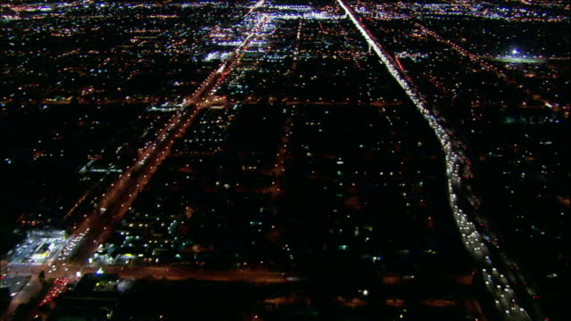 Camera glides southward over San Fernando Valley above 405 Freeway; tilts up to reveal constellation of lights.
