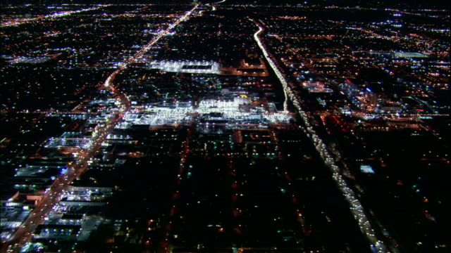 Camera glides southward over San Fernando Valley above 405 Freeway. Midway through glides over brightly lit car dealership.
