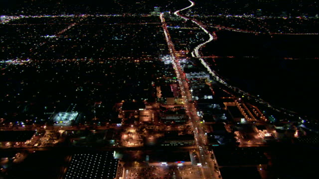 Camera glides southward over San Fernando Valley and constellation of lights. 405 freeway, like a river of white light, snakes through frame right. Camera tilts up to reveal Sepulveda Pass.