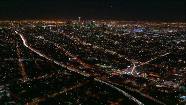 Camera glides towards distant skyscrapers of downtown Los Angeles; sea of lights in f.g.