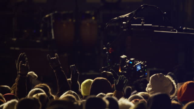 A RED camera hangs above a crowd of spectators from a tulip crane during a concert event.