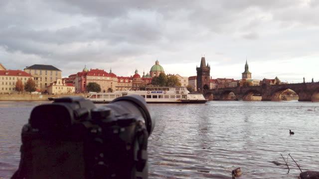 vídeos de stock, filmes e b-roll de a câmera está tomando o lapso de tempo do rio de vltava e da ponte de charles no por do sol em praga em república checa - mala strana