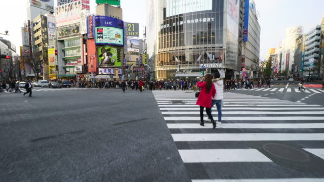 camera is walking through the shibuya intersection to go to shibuya center on saturday evening.and captures the cityscape and pedestrians, while crossing the intersection. - トラッキングショット点の映像素材/bロール