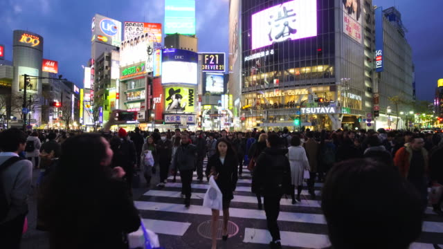 camera is walking through the shibuya intersection to go to shibuya center on saturday evening at dusk.and captures the night cityscape and pedestrians while crossing the intersection. - tracking shot stock videos & royalty-free footage